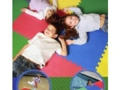 A photo of three children laying head to head on multi-colored puzzle flooring. Two smaller photos are superimposed in circles which show the flooring near a pool and in a gym