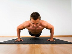 photo of a man without a shirt doing push-ups on a Norsk flooring mat